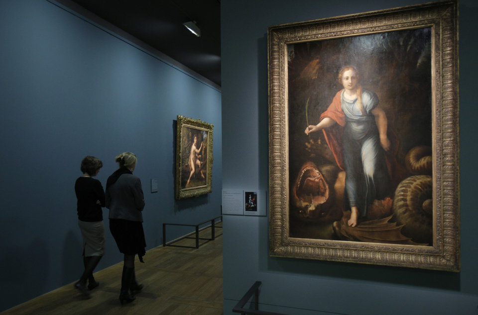 "Women walk past "" Sainte Marguerite"", a painting by Raphael as part of the exhibition ""Late Raphael"" at the Louvre museum, in Paris, Tuesday, Oct. 9, 2012. This exhibition, organized by the Louvre from Oct. 11 to Jan. 14, 2013 in partnership with the Prado Museum, brings together the works produced by Raphael in Rome during the last years of his life. (AP Photo/Christophe Ena)"