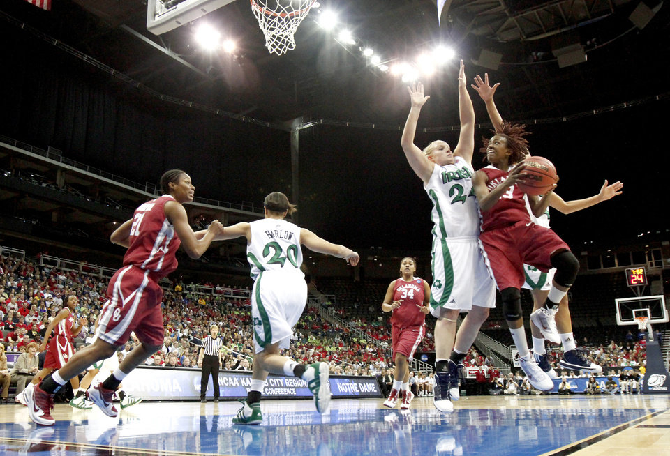 Photo - OU's Danielle Robinson goes to the basket past Notre Dame's Lindsay Schrader during the Sweet 16 round of the NCAA women's  basketball tournament in Kansas City, Mo., on Sunday, March 28, 2010. 
