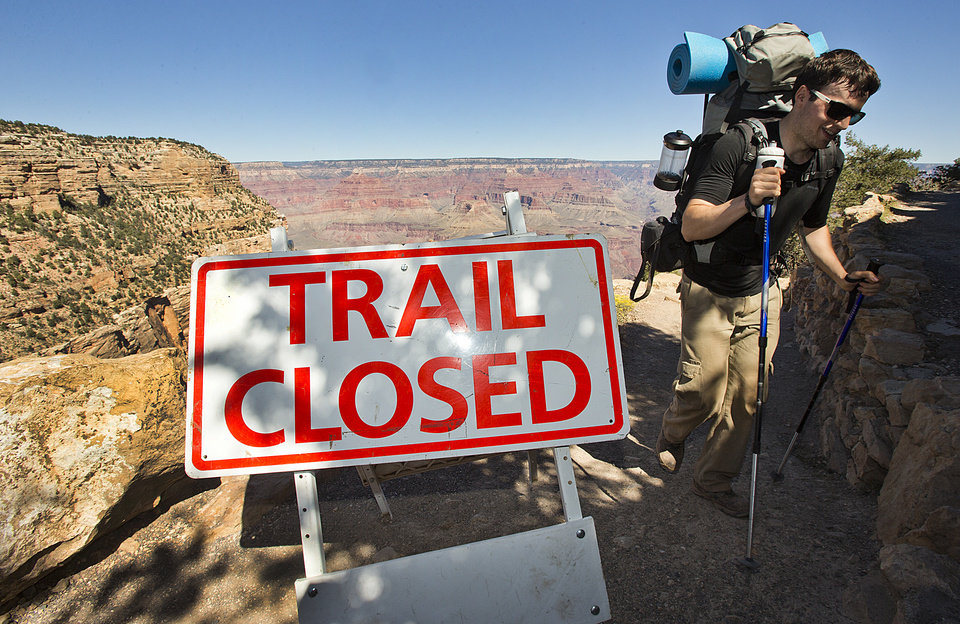 Photo - Grand Canyon Park Closed-10-1-2013- Sebastian Ramirez, 27, of Austin, Texas, hikes out of the Bright Angel Trail in Grand Canyon National Park, Tuesday afternoon.  Ramirez spent the night with friends in the bottom of the Canyon at Bright Angel Campground. Beginning at 6 am, visitors were told the park was closed and they could not visit.    (AP Photo/The Arizona Republic, Tom Tingle)  MARICOPA COUNTY OUT; MAGS OUT; NO SALES   MBO