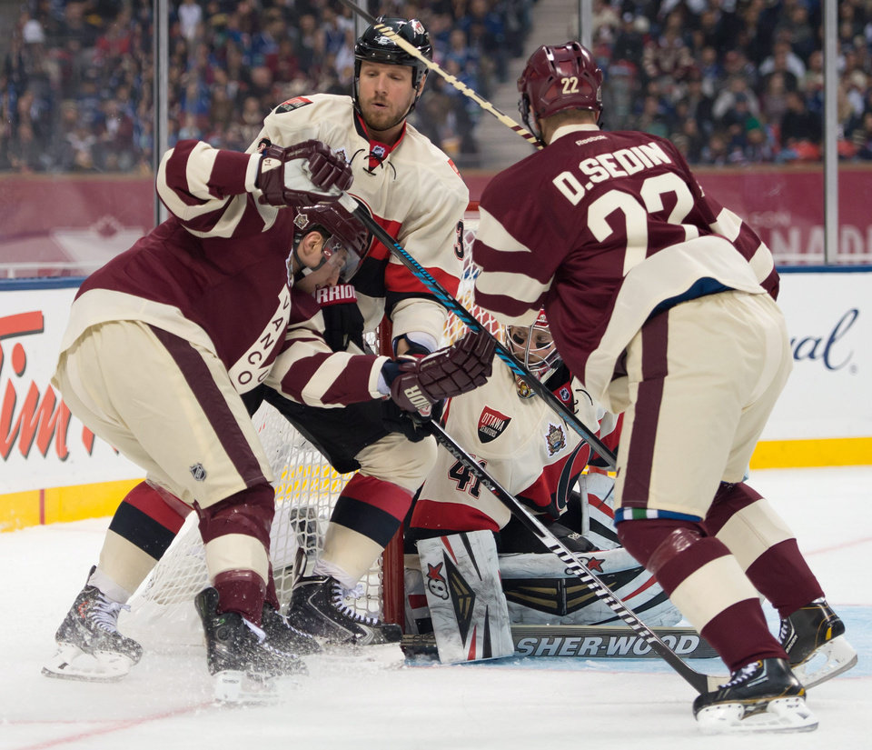 Photo - Vancouver Canucks' Alex Burrows, left, is checked by Ottawa Senators' Marc Methot, second from left, as goalie Craig Anderson and Canucks' Daniel Sedin, of Sweden, watch during the second period of the NHL Heritage Classic hockey game in Vancouver, British Columbia,, on Sunday, March 2, 2014. (AP Photo/The Canadian Press, Jonathan Hayward)