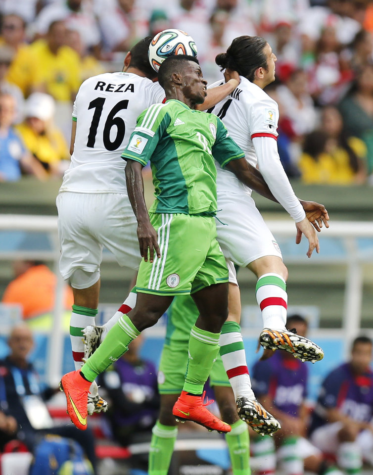 Photo - Nigeria's Ramon Azeez goes up against Iran's Reza Ghoochannejhad (16) and Andranik Teymourian during the group F World Cup soccer match between Iran and Nigeria at the Arena da Baixada in Curitiba, Brazil, Monday, June 16, 2014.  (AP Photo/Frank Augstein)