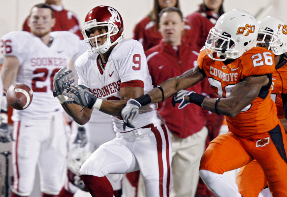 Photo - Oklahoma State's Quinton Moore (26) breaks up a pass for Oklahoma's Juaquin Iglesias (9) during the first half of the college football game between the University of Oklahoma Sooners (OU) and Oklahoma State University Cowboys (OSU) at Boone Pickens Stadium on Saturday, Nov. 29, 2008, in Stillwater, Okla. STAFF PHOTO BY CHRIS LANDSBERGER