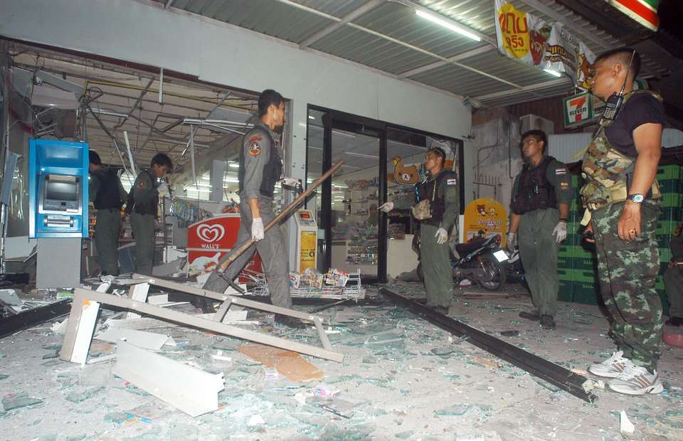 Photo - Thai police officers and soldiers examine the site where a bomb exploded at a super store in Pattani province, southern Thailand Saturday, May 24, 2014 Police say at least nine bombs have exploded in Thailand's restive south, killing two people and wounding dozens. The blasts were in a southern province that is facing an Islamic insurgency. (AP Photo/Sumeth Panpetch)