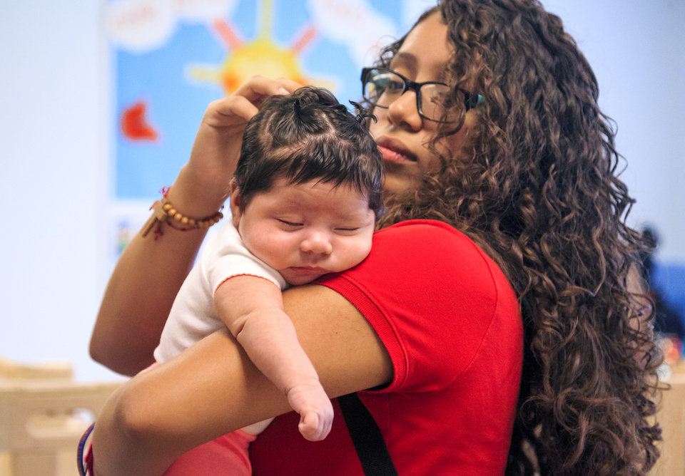 Photo -  High school student Sayra Perez is able to visit her baby, Zeleyna Lopez, during school because of the new childcare center at U.S. Grant High School. [Photo by Chris Landsberger, The Oklahoman]