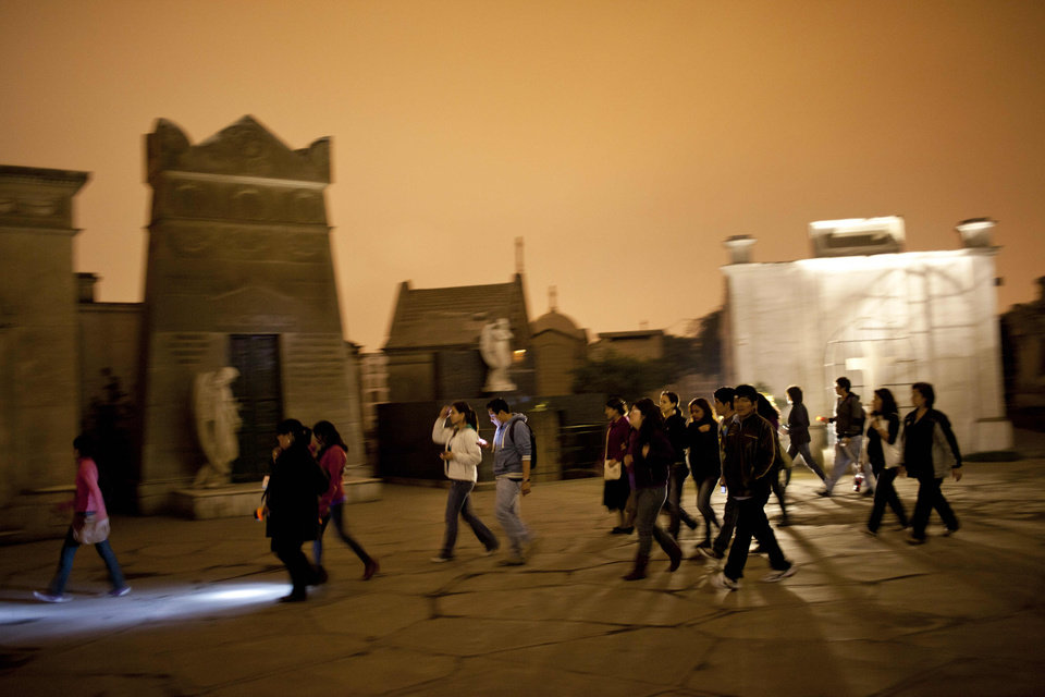 In this Dec. 6, 2012 photo, people take a nighttime guided tour through the Presbitero Matias Maestro cemetery in Lima, Peru. The cemetery, created by one of the last Spanish viceroys, was established the outside the walls of old Lima. (AP Photo/Rodrigo Abd)