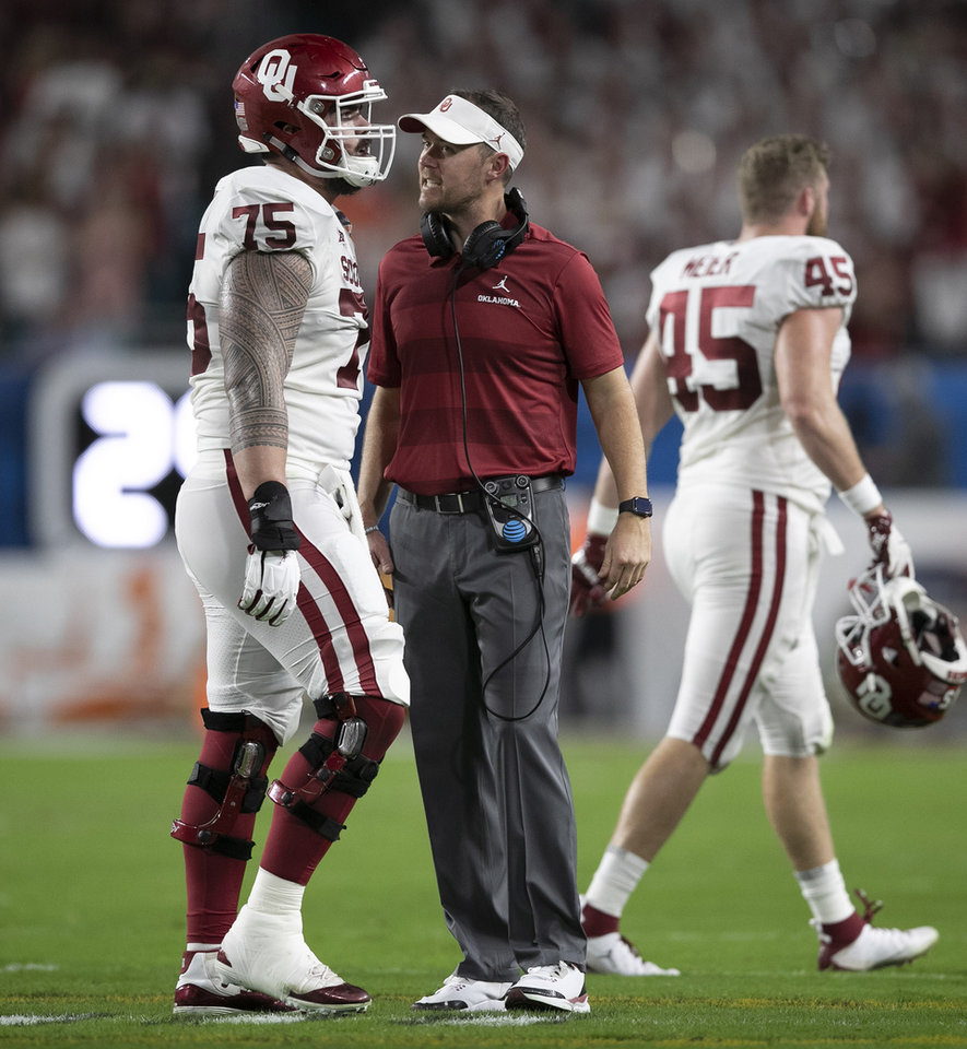 Photo - Oklahoma Sooners head coach Lincoln Riley talks with Oklahoma Sooners offensive lineman Dru Samia (75) after two unsportsmanlike conduct penalties in the second quarter in the College Football Playoff semifinals in the Orange Bowl at Hard Rock Stadium in Miami Gardens, Florida on December 29, 2018. [ALLEN EYESTONE/palmbeachpost.com]
