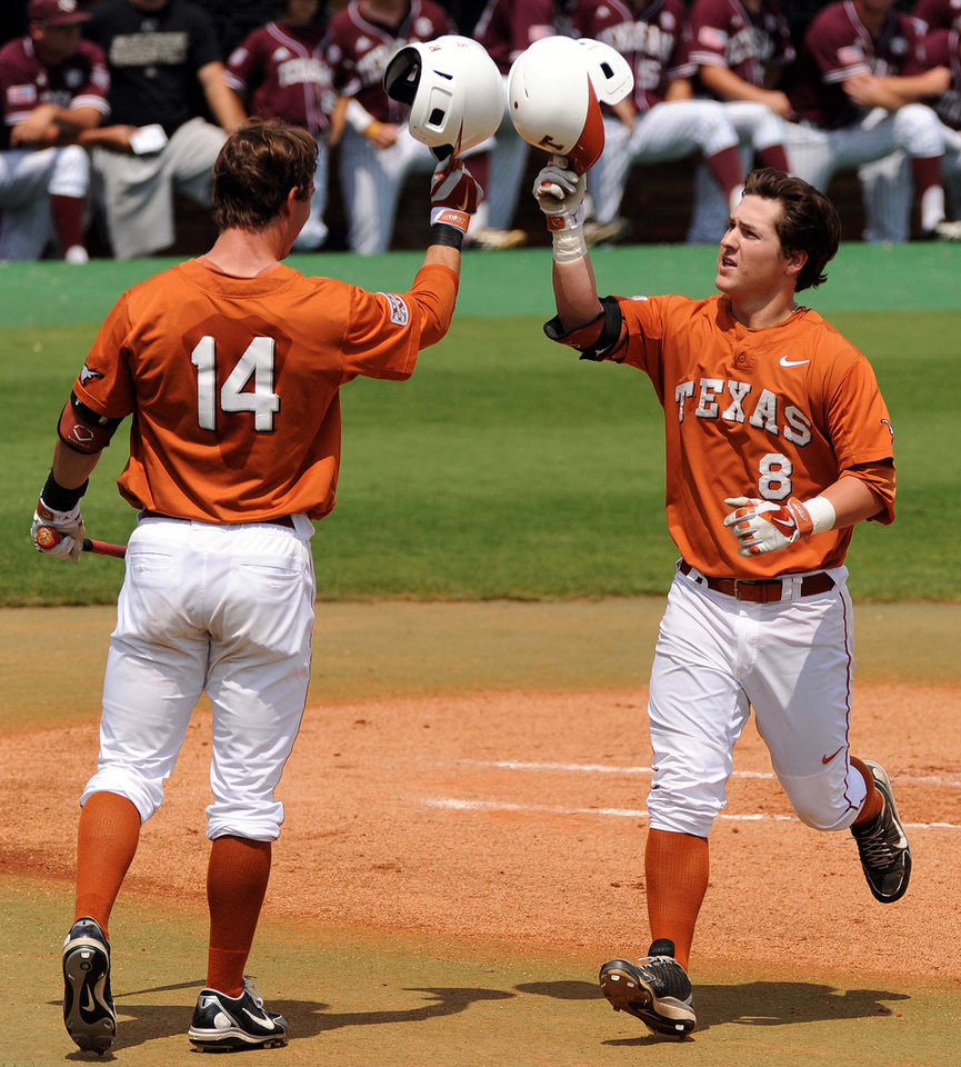 Photo - Texas' Brooks Marlow, right, celebrates his solo home run with Ben Johnson during the first inning against Texas A&M in an NCAA college baseball tournament regional game Friday, May 30, 2014, at Reckling Park in Houston. (AP Photo/Houston Chronicle, Eric Christian Smith) MANDATORY CREDIT