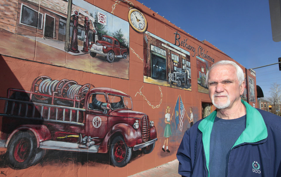 Above: Bob Palmer, a muralist who lives in Bethany, has painted murals on the sides of buildings along State Highway 66. He stands next to one of his murals Thursday in Bethany.
