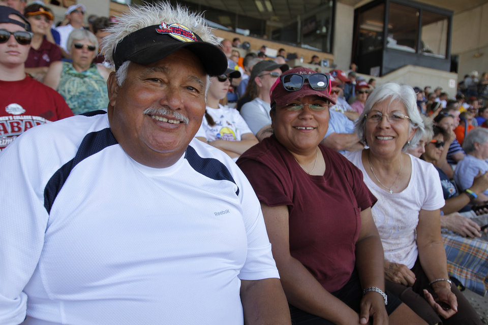 Leno Ramirez, of Austin, Texas, sits with his daughter, Lena, and wife, Hope, during a Women\'s College World Series game between Tennessee and Oregon at ASA Hall of Fame Stadium in Oklahoma City, Saturday, June 2, 2012. Ramirez has been attending the WCWS for 17 years. Photo by Garett Fisbeck, The Oklahoman