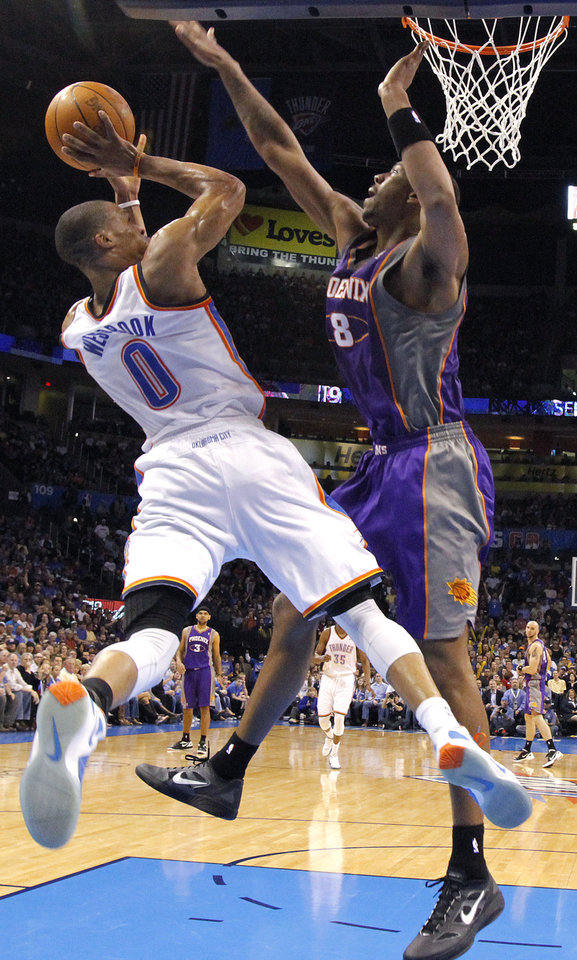 Oklahoma City Thunder point guard Russell Westbrook (0) puts up a shot over Phoenix Suns center Channing Frye (8) during the NBA basketball game between the Oklahoma City Thunder and the Phoenix Suns at the Chesapeake Energy Arena on Wednesday, March 7, 2012 in Oklahoma City, Okla.  Photo by Chris Landsberger, The Oklahoman