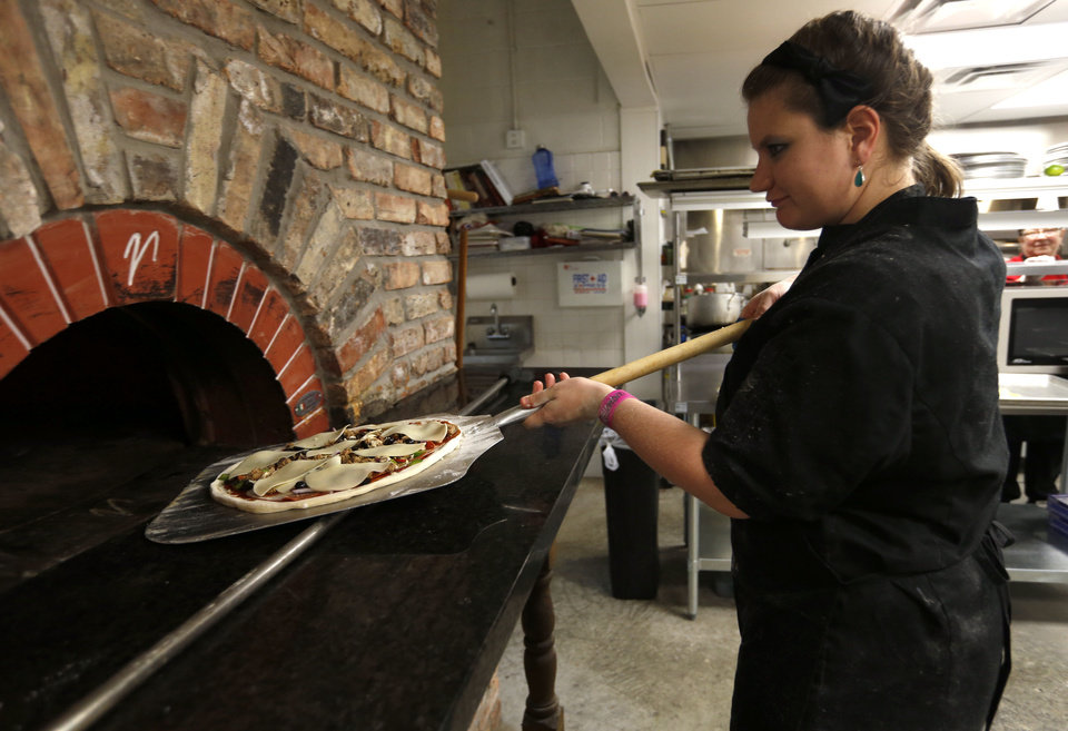 Photo - Ashton Muhs puts a wood-burning stove at Gabriella's Italian Grill and Pizzeria at the old County Line building on 1226 NE 63 in Oklahoma City, Friday, July 13, 2012. Photo by Sarah Phipps, The Oklahoman. ORG XMIT: OKOKL  SARAH PHIPPS - SARAH PHIPPS