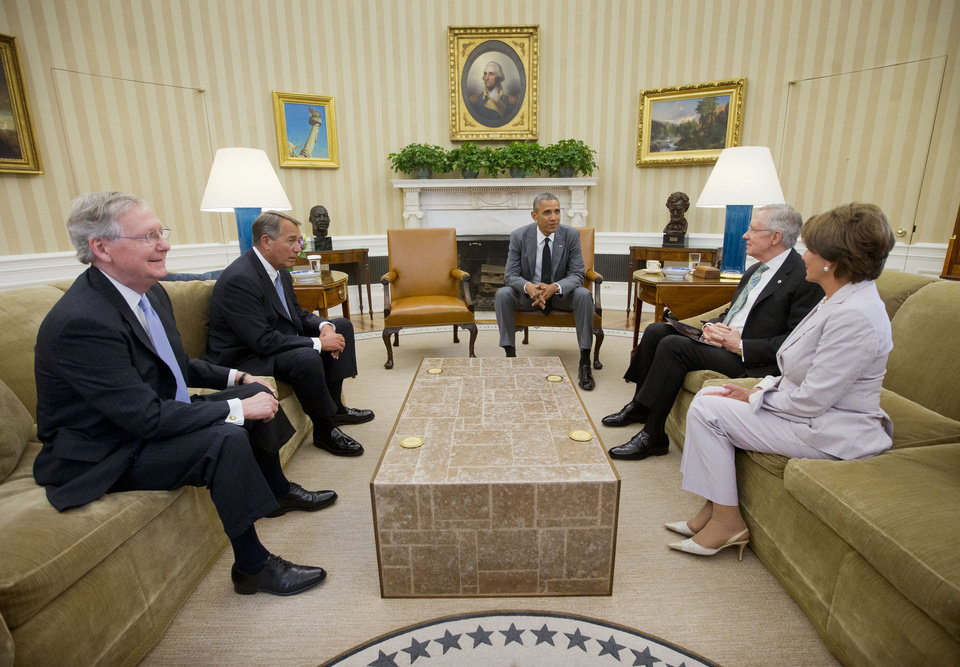 Photo - President Barack Obama meets with, from left, Senate Minority Leader Mitch McConnell of Ky., House Speaker John Boehner of Ohio, Senate Majority Leader Harry Reid of Nev., and House Minority Leader Nancy Pelosi of Calif., in the Oval Office of the White House in Washington, Wednesday, June 18, 2014. Obama briefed leaders of Congress on US options for blunting an Islamic insurgency in Iraq. US officials say Obama is not yet prepared to move forward with strikes and is instead focused on increased training for Iraq's security forces, boosting Iraqi intelligence capacities and upgrading equipment. (AP Photo/Pablo Martinez Monsivais)