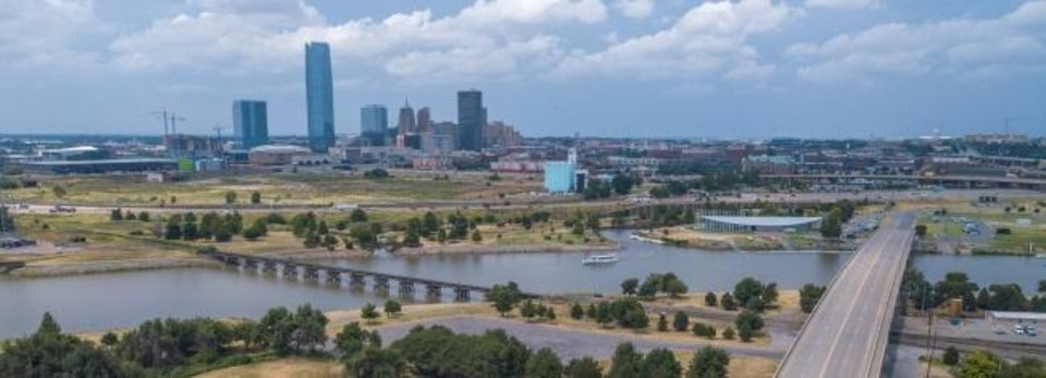 Photo -  In this drone image from south of the Oklahoma River looking toward the Oklahoma City skyline, the Chesapeake Boathouse can be seen on the right next to the river. The edge of Pull-A-Part is just visible on the far left between the river and Interstate 40. [DAVE MORRIS/THE OKLAHOMAN]