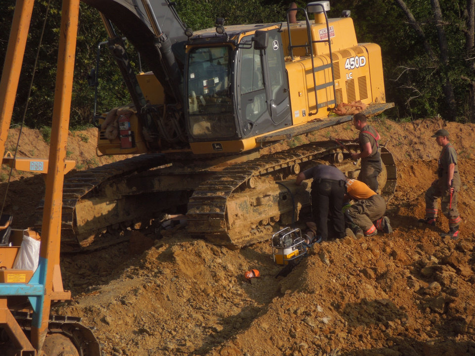 Photo - Authorities work to remove protesters who locked themselves to an excavator Monday near Seminole to protest construction of the Keystone XL pipeline. Photo provided