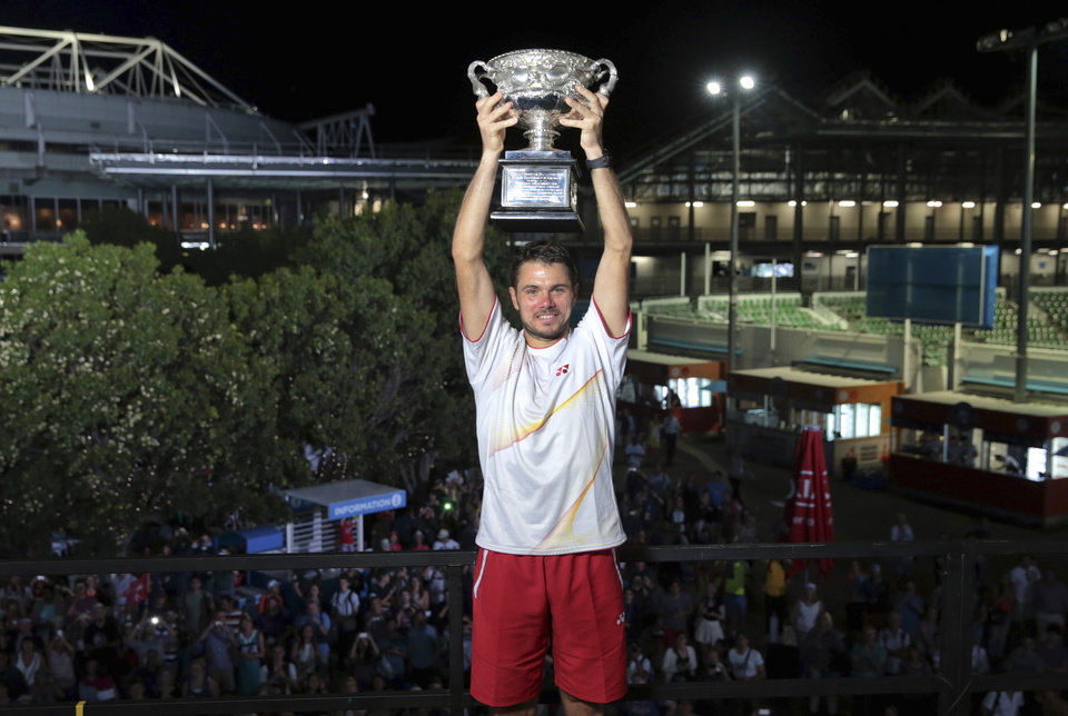 Photo - In this photo released by Tennis Australia, Stanislas Wawrinka of Switzerland holds his trophy aloft after defeating Spain's Rafael Nadal to win the men's singles title at the Australian Open tennis championship in Melbourne, Australia, Sunday, Jan. 26, 2014.  (AP Photo/Tennis Australia,Fiona Hamilton)
