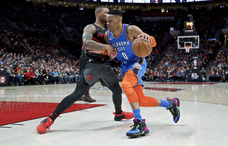 Photo - Oklahoma City Thunder guard Russell Westbrook, right, drives Portland Trail Blazers guard Damian Lillard during the first half of an NBA basketball game in Portland, Ore., Thursday, March 7, 2019. (AP Photo/Craig Mitchelldyer)