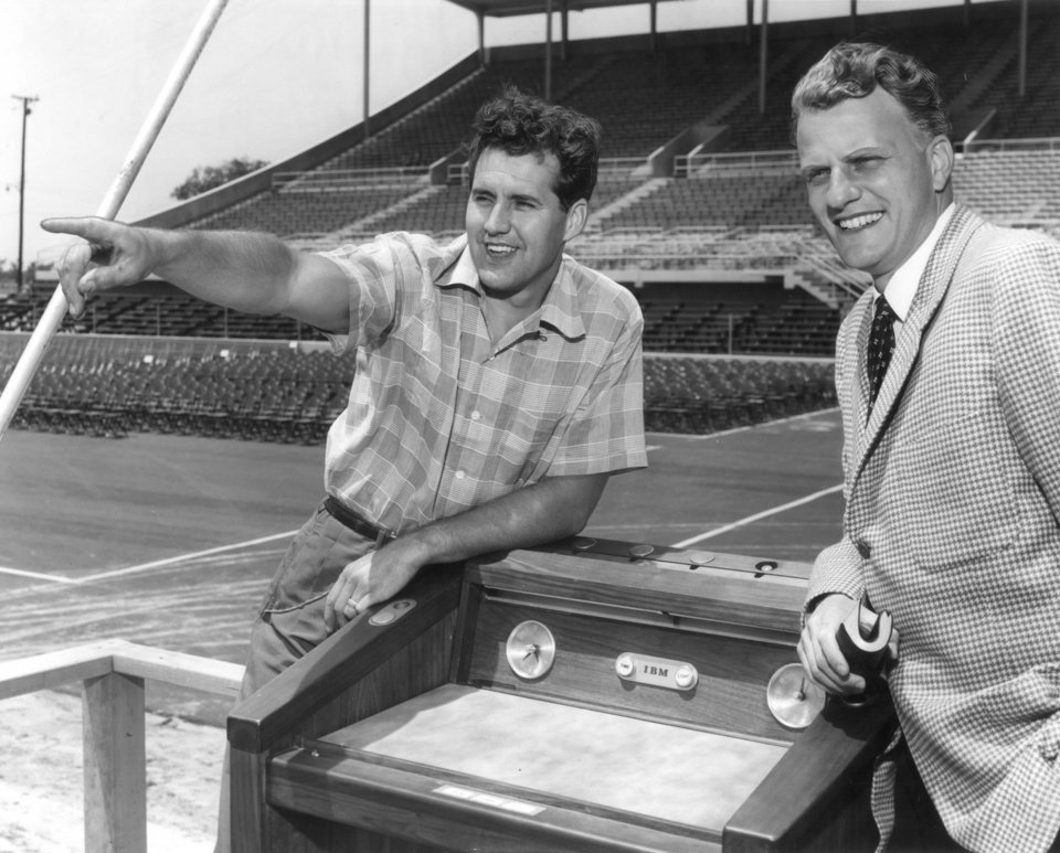 """Photo - Billy Graham and his director of music, Cliff Barrows, left, make a final check of the fairground facilities. They are leaning on Graham's specially-constructed electric podium. The unusual podium (a gift) contains a clock, a timing device and a push-button control for height adjustment. Evangelist Billy Graham in Oklahoma City.  Staff photo by  Richard """"Dick"""" Peterson taken 6/2/1956."""