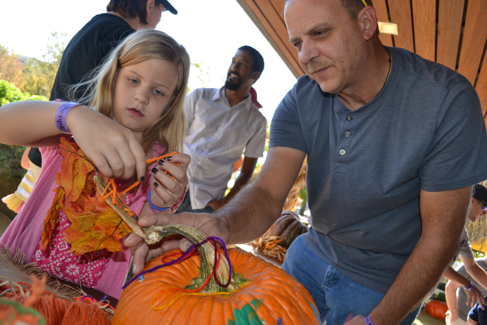 Alisabeth Covey, nine, and her dad, Preston, of Moore, tie a ponytail of autumn leaves to the stem of her decorated pumpkin Saturday at Pumpkinville in downtown Oklahoma City. PHOTO BY ZEKE CAMPFIELD, THE OKLAHOMAN <strong>Zeke Campfield - Zeke Campfield</strong>