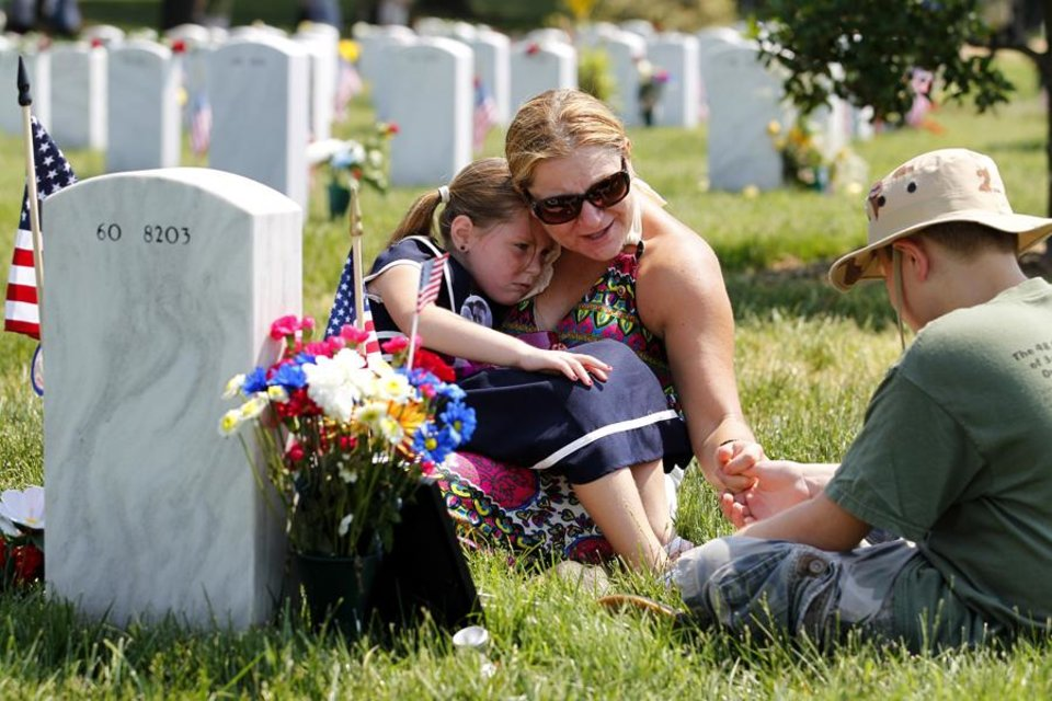 Photo -  Laura Youngblood comforts her son Hunter, 10, and daughter Emma, 5, at the grave of her husband Travis L. Youngblood at Section 60 in Arlington National Cemetery, Monday, May 30, 2011. (AP Photo/Jose Luis Magana) ORG XMIT: DCJL118