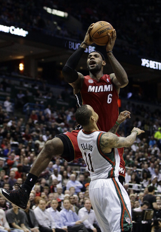 Photo - Miami Heat's LeBron James, top, shoots over Milwaukee Bucks' Monta Ellis (11) during the second half of Game 3 in their first-round NBA basketball playoff series on Thursday, April 25, 2013, in Milwaukee. The Heat won 104-91 to take a 3-0 lead in the series. (AP Photo/Aaron Gash)
