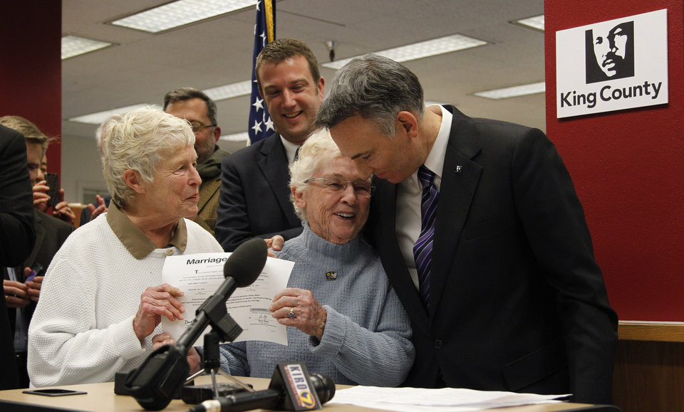Photo - King County Executive Dow Constantine, right, leans down to embrace Pete-e Petersen as her partner, Jane Abbott Lighty, watches after Constantine issued them the first marriage license to a same-sex couples, Thursday, Dec. 6, 2012, in Seattle. Constantine began issuing the licenses immediately upon certification of the November election that passed Referendum 74. (AP Photo/Elaine Thompson)