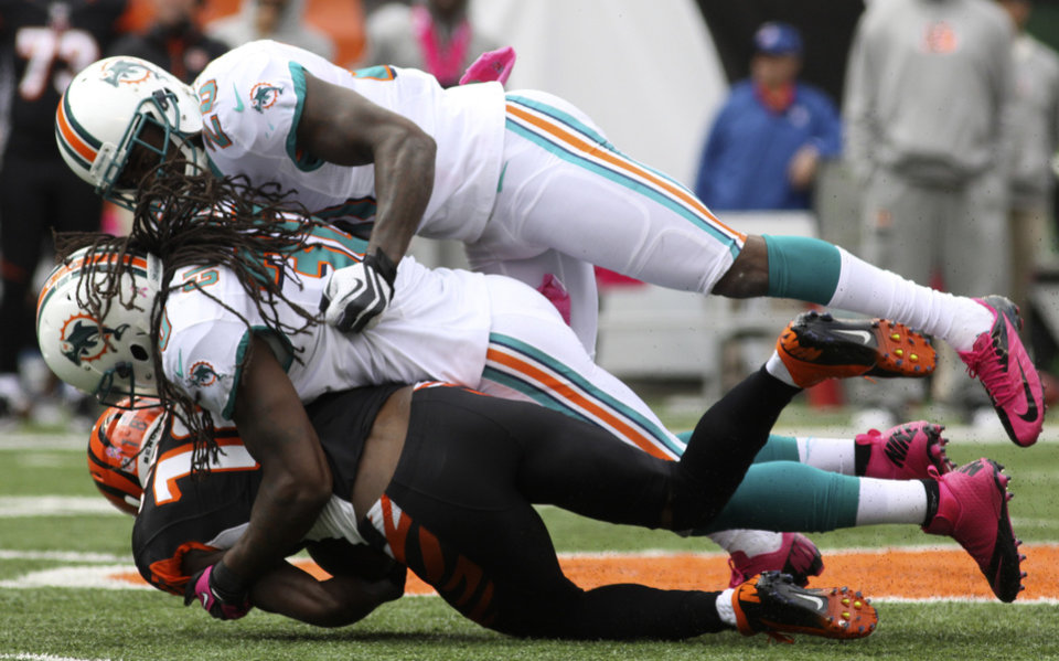 Photo -   Cincinnati Bengals wide receiver A.J. Green, bottom, is tackled by Miami Dolphins strong safety Chris Clemons and free safety Reshad Jones, top, after a gain in the first half of an NFL football game, Sunday, Oct. 7, 2012, in Cincinnati. (AP Photo/Tom Uhlman)