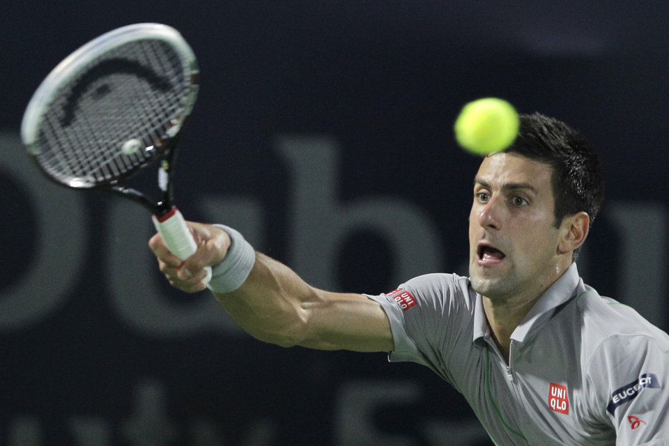 Photo - Novak Djokovic of Serbia returns the ball to Roger Federer of Switzerland during a semi final match of the Dubai Duty Free Tennis Championships in Dubai, United Arab Emirates, Friday, Feb. 28, 2014. (AP Photo/Kamran Jebreili)