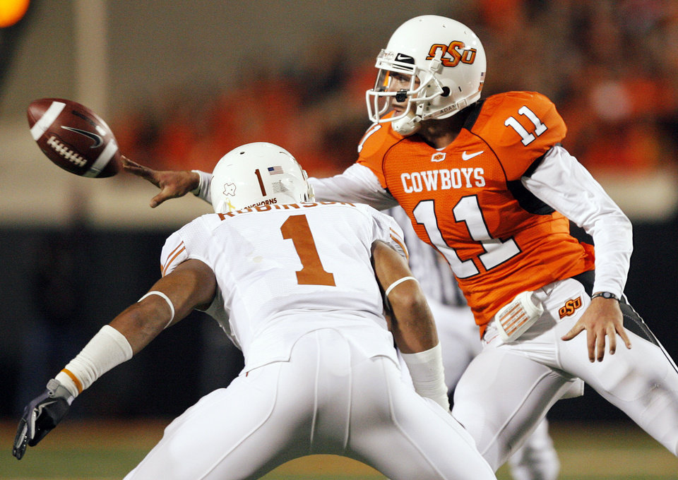 Photo - OSU's Zac Robinson (11) pitches the ball past Keenan Robinson (1) of UT to OSU's Keith Toston (not pictured) in the second quarter of the college football game between the Oklahoma State University Cowboys (OSU) and the University of Texas Longhorns (UT) at Boone Pickens Stadium in Stillwater, Okla., Saturday, Oct. 31, 2009. Photo by Nate Billings, The Oklahoman