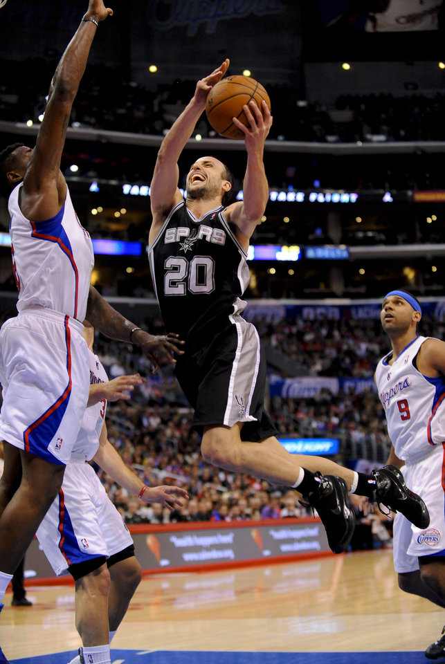 Photo - San Antonio Spurs guard Manu Ginobili (20), of Argentina, drives on Los Angeles Clippers center DeAndre Jordan, left, for a basket in the first half of a NBA basketball game, Tuesday, Feb. 18, 2014, in Los Angeles.(AP Photo/Gus Ruelas)