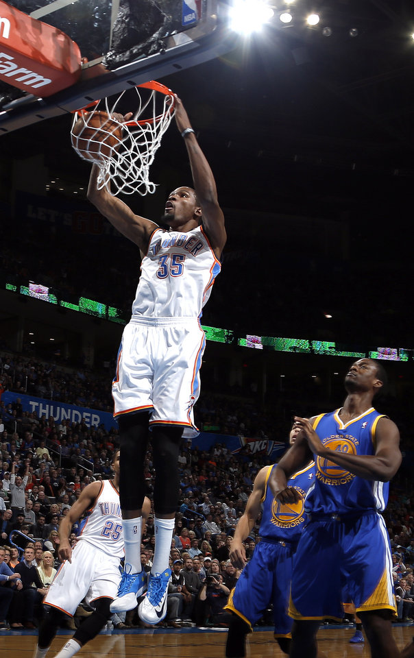 Oklahoma City's Kevin Durant (35) dunks in front of Golden State's Harrison Barnes (40) during the NBA game between the Oklahoma City Thunder and the Golden State Warriors at the Chesapeake Energy Arena, Friday, Nov. 29, 2013. Photo by Sarah Phipps, The Oklahoman