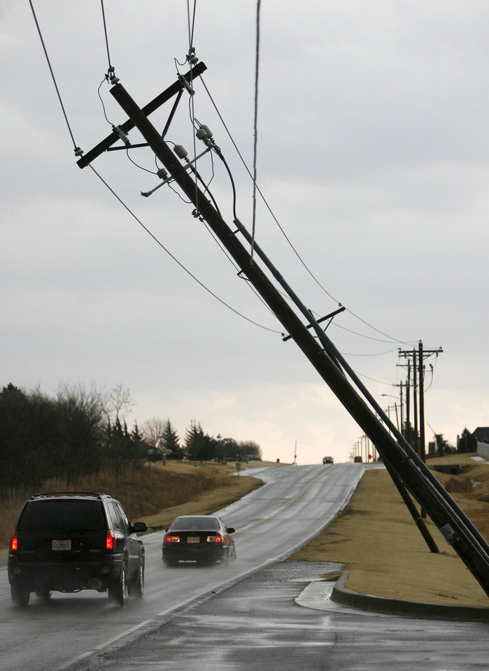 Photo - Cars drive past a leaning utility line on Covell in Edmond, Okla., after a storm, Tuesday, Feb. 10, 2009. PHOTO BY BRYAN TERRY, THE OKLAHOMAN