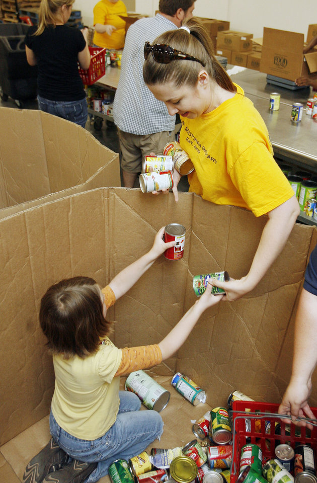 Photo - GABI GUYSE: Sheri Guyse and 8-year-old daughter Gabi, with the OKC Midtown Rotary, volunteer their time at the Regional Food Bank in Oklahoma City, OK, Saturday, June 6, 2009. By Paul Hellstern, The Oklahoman ORG XMIT: KOD