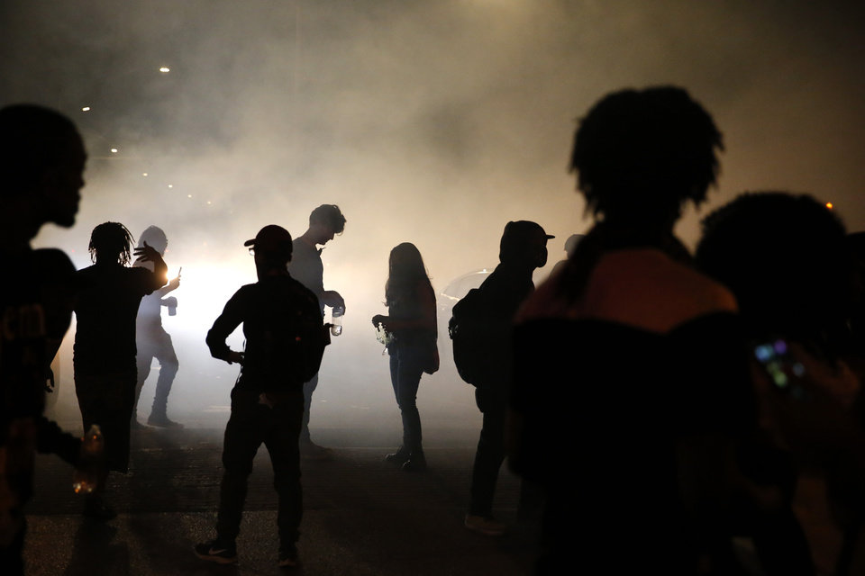 Photo - Protesters are silhouetted by the smoke of a burn out from a car in the intersection of 23rd and Classen in Oklahoma City, Saturday, May 30, 2020. The protest was in response to the death of George Floyd. [Sarah Phipps/The Oklahoman]