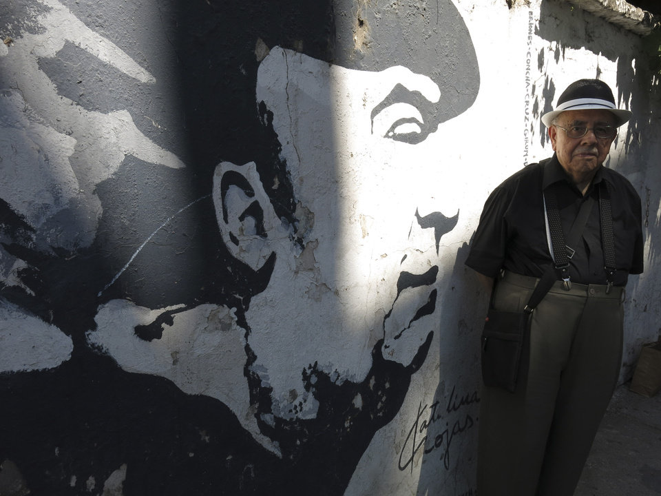 Photo - Hernan Loyola, a friend of Chilean Nobel laureate Pablo Neruda, poses for a photo in front of a mural of Neruda painted on a wall near the poet's home in, Santiago, Chile, Friday, Nov. 8, 2013. Loyola, who is considered one of the world's top experts in Neruda literature, has also written several books about the poet. The four-decade mystery of whether Neruda was poisoned was seemingly cleared up on Friday, when forensic test results showed no chemical agents in his bones. But his family and driver were not satisfied and said they'll request more proof. (AP photo/Luis Andres Henao)