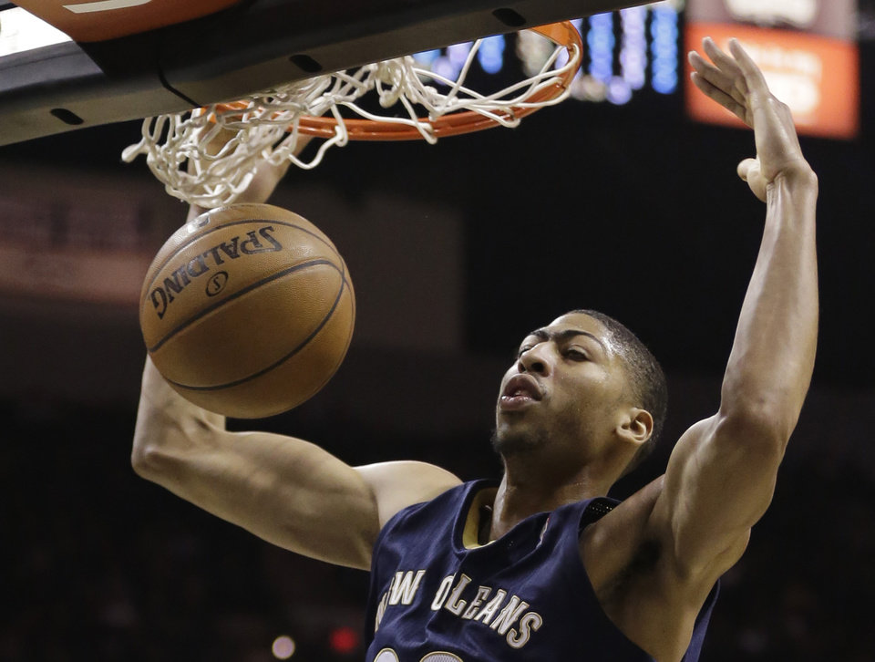 Photo - New Orleans Pelicans' Anthony Davis scores against the San Antonio Spurs during the first half of an NBA basketball game, Monday, Nov. 25, 2013, in San Antonio. (AP Photo/Eric Gay)