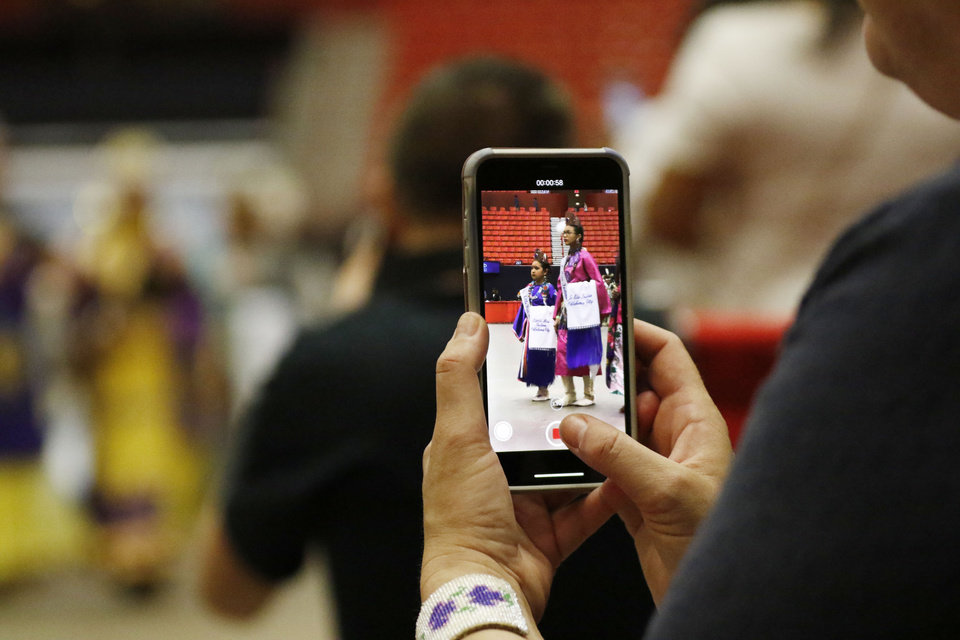 Photo - An attendee takes a video of the Grand Entry of Dancers at 2019 Red Earth Festival at the Cox Convention Center in Oklahoma City, Oklahoma Saturday, June 8, 2019.  [Paxson Haws/The Oklahoman]