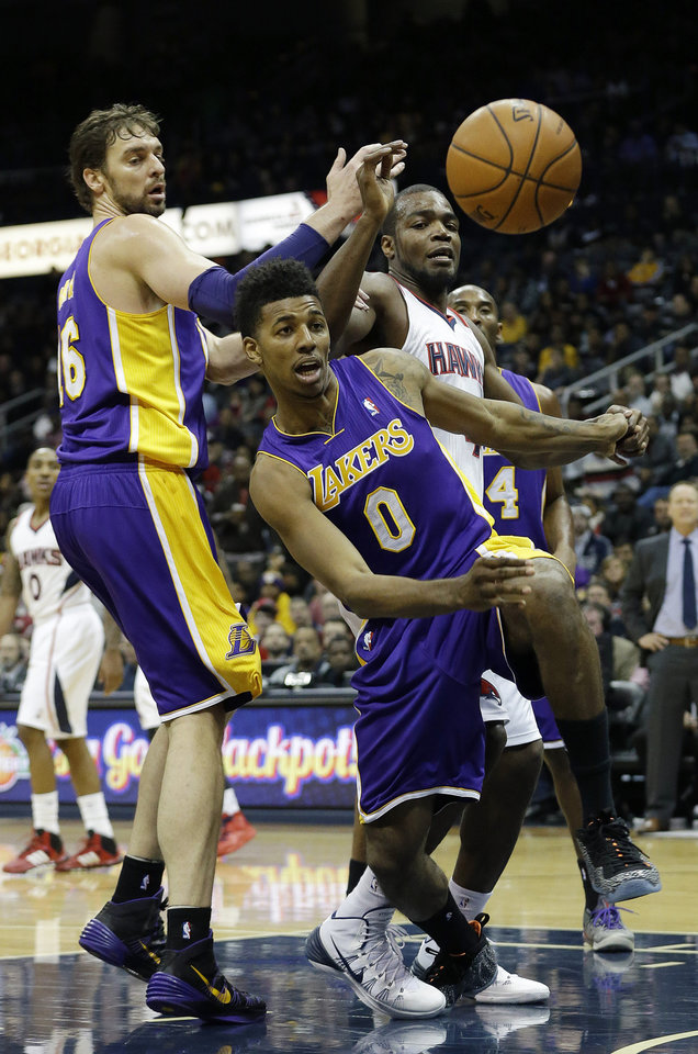 Atlanta Hawks' Paul Milsap, center right, chases the loose ball with Los Angeles Lakers' Nick Young (0) and Pau Gasol (16)  in the first half of an NBA basketball game, Monday, Dec. 16, 2013, in Atlanta. (AP Photo/John Bazemore)