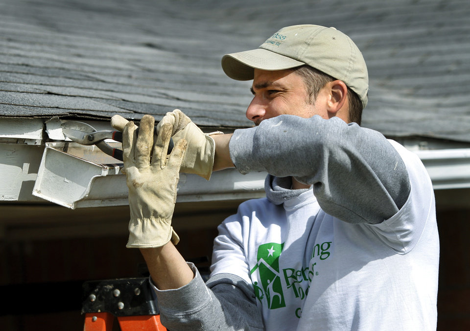 Brad Schatzel uses tin snips to cut flashing behind a section of guttering on the front of the home. About 40 members of Mayflower Congregational Church volunteered their time Saturday, April 13, 2013, and brought hammers, drills, paintbrushes, screwdrivers, rakes, brooms and other tools to give the home of Charles Owens a major facelift inside and out. This was part of a project called Rebuilding Together OKC. Owens' home is in the 600 block of N. Nebraska in northeast Oklahoma City.    by Jim Beckel, The Oklahoman.