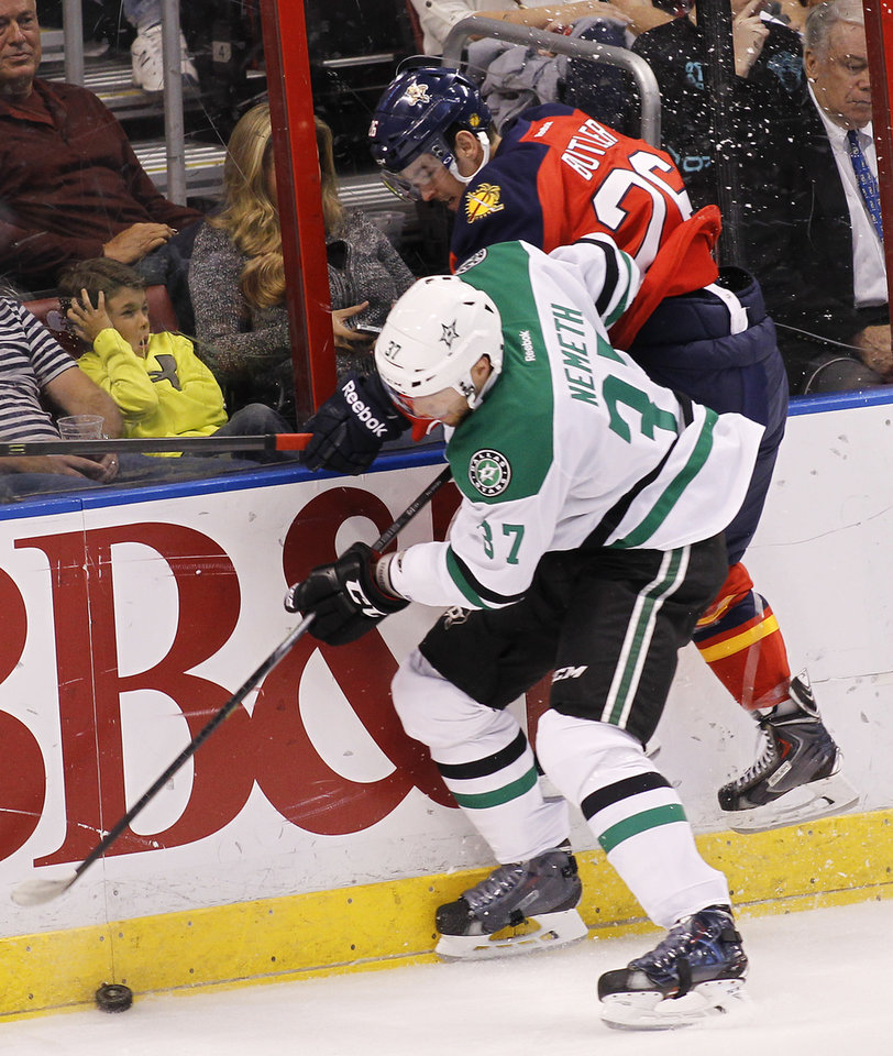 Photo - Dallas Stars defenseman Patrik Nemeth (37) and Florida Panthers right wing Bobby Butler (26) collide as they go for the puck during the first period of an NHL hockey game in Sunrise, Fla., Sunday, April 6, 2014. (AP Photo/Terry Renna)