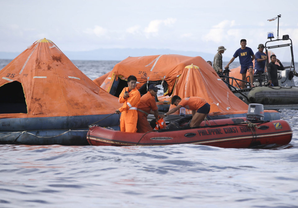 Photo - A cluster of life rafts is seen floating near the cargo ship Sulpicio Express Siete Saturday Aug. 17, 2013, a day after the cargo ship collided with a passenger ferry off the waters of Talisay city, Cebu province in central Philippines. Divers combed through a sunken ferry Saturday to retrieve the bodies of more than 200 people still missing from an overnight collision with a cargo vessel near the central Philippine port of Cebu that sent passengers jumping into the ocean and leaving many others trapped. At least 28 were confirmed dead and hundreds rescued. (AP Photo/Bullit Marquez)