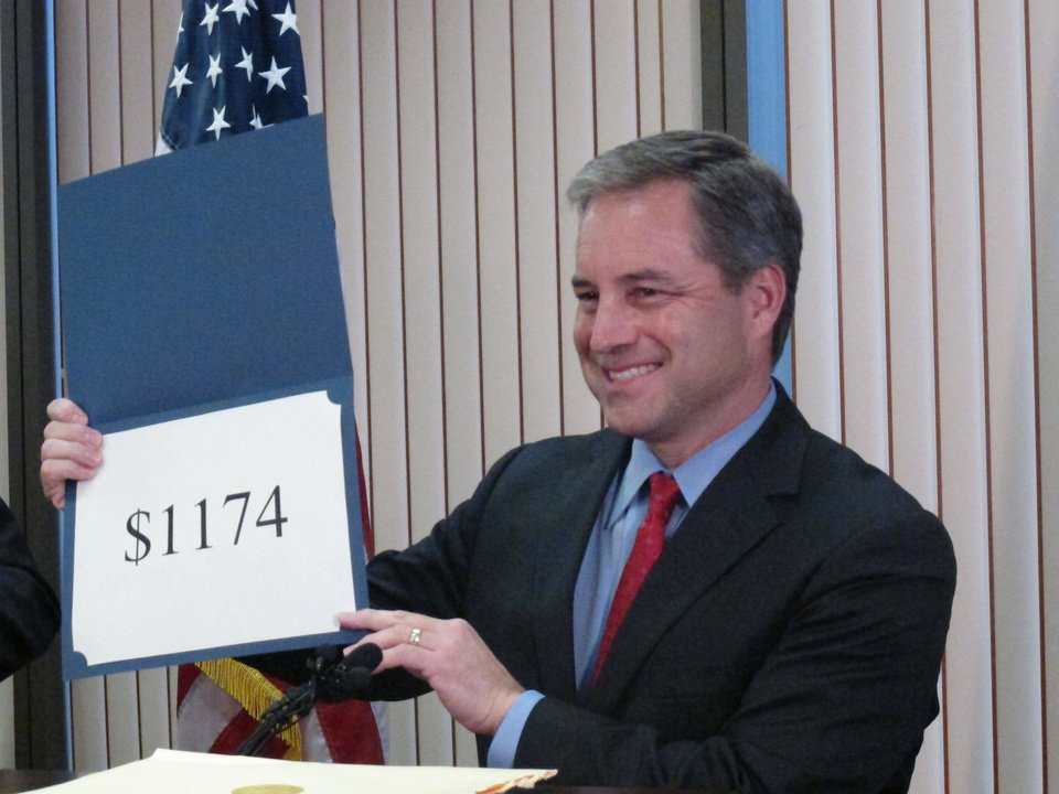 Alaska Gov. Sean Parnell holds up a sign with the amount of this year\'s Alaska Permanent Fund Dividend checks during a news conference Tuesday, Sept. 20, 2011, in Anchorage, Alaska. The checks will begin appearing in Alaskans\' bank accounts on Oct. 6, 2011. Last year\'s amount was $1,281. (AP Photo/Mark Thiessen)
