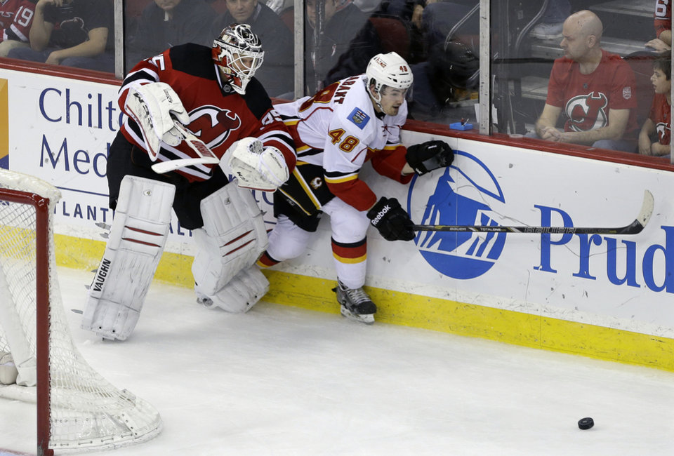 Photo - Calgary Flames' Bryce Van Brabant (48) skates after the puck away from New Jersey Devils goalie Cory Schneider (35) during the second period of an NHL hockey game in Newark, N.J., Monday, April 7, 2014. (AP Photo/Mel Evans)