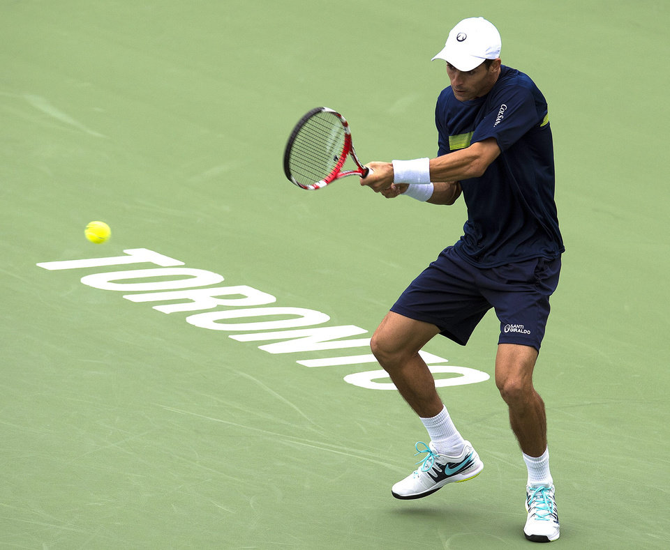 Photo - Santiago Giraldo of Colombia hits a backhand to Nick Kyrgios of Australia in Rogers Cup tennis action in Toronto on Tuesday, Aug. 5, 2014. (AP Photo/The Canadian Press, Frank Gunn)