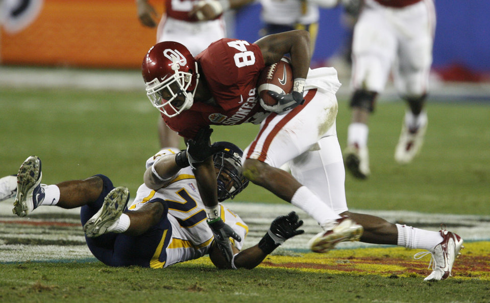 Photo - Quentin Chaney runs after a catch past Brandon Hogan during the first half of the Fiesta Bowl college football game between the University of Oklahoma Sooners (OU) and the West Virginia University Mountaineers (WVU) at The University of Phoenix Stadium on Wednesday, Jan. 2, 2008, in Glendale, Ariz. 