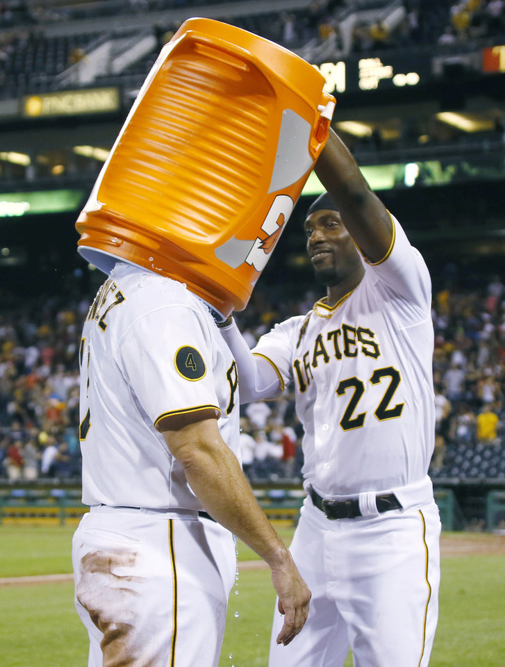 Photo - Pittsburgh Pirates' Andrew McCutchen puts a bucket over the head of Gaby Sanchez after he and Josh Harrison dumped ice water over Sanchex who drove in the game winning run with a sacrifice fly in the bottom of the ninth inning of the baseball game against the Atlanta Braves on Wednesday, Aug. 20, 2014, in Pittsburgh. The Pirates won 3-2. (AP Photo/Keith Srakocic)