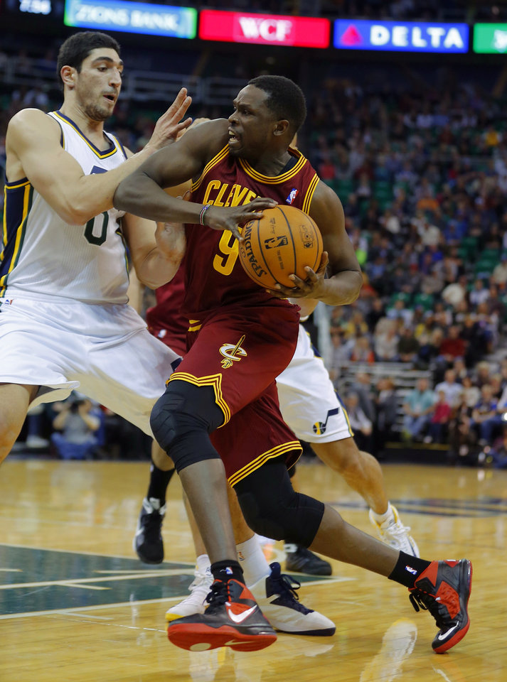 Photo - Cleveland Cavalier's Luol Deng, right, drives to the basket on Utah Jazz's Enes Kantor during an NBA basketball game in Salt Lake City, Friday, Jan. 10, 2014. (AP Photo/George Frey)