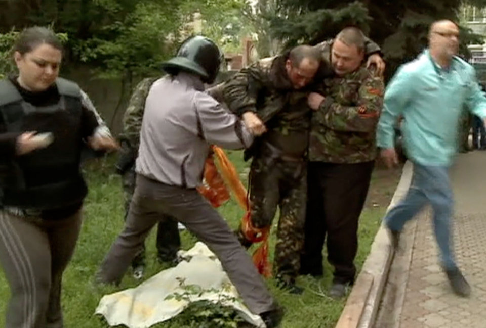 Photo - In this image taken from Rossia 24 television channel TV, an injured Ukrainian military helicopter pilot is assisted by pro-Russian activists after he was shot down in Slovyansk, eastern Ukraine, Friday May 2, 2014. Pro-Russia forces shot down two Ukrainian helicopters Friday as Ukraine launched its first major offensive against an insurgency that has seized government buildings in the east. The Kremlin said Kiev's move against the insurgents