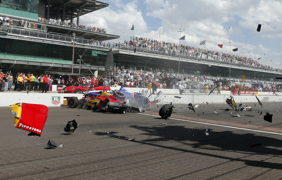 Photo - Sebastian Saavedra, left, of Colombia,  is hit by Mikhail Aleshin, of Russia,  at the start of the inaugural Grand Prix of Indianapolis IndyCar auto race at the Indianapolis Motor Speedway in Indianapolis, Saturday, May 10, 2014. (AP Photo/Robert Baker)