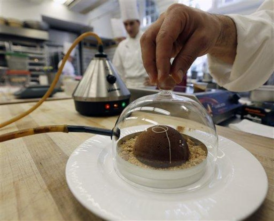 Photo - In this image taken on Friday, Sept. 14, 2012, cinnamon aroma is added to a peanut butter and milk chocolate dome dessert at the Culinary Institute of America in Hyde Park, N.Y. This esteemed cooking school north of New York City is dramatically pumping up science instruction, saying that tomorrow's chefs will need more technical know-how in the age of molecular gastronomy and sous-vide. (AP Photo/Mike Groll)