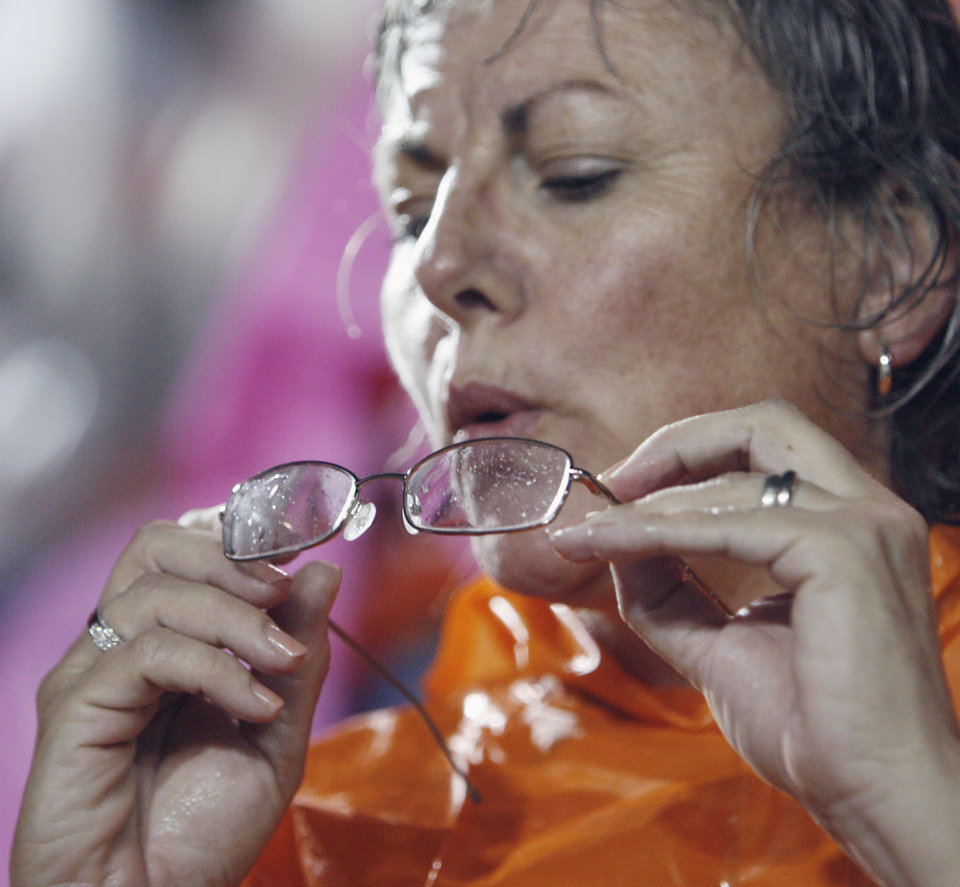 Ann Bailey of Mustang tries to clear her glasses during the rain delay before the first half of the college football game between the Troy University Trojans and the Oklahoma State University Cowboys at Movie Gallery Veterans Stadium in Troy, Ala., Friday, September 14, 2007. BY STEVE SISNEY, THE OKLAHOMAN